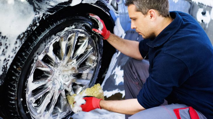 man washing car wheel with sponge soap